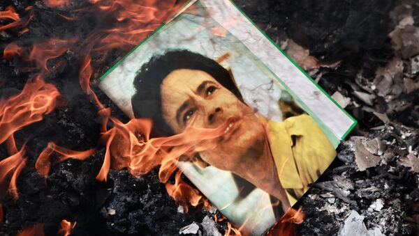 A portrait of Muammar Gaddafi burning in a fire. - Sputnik International