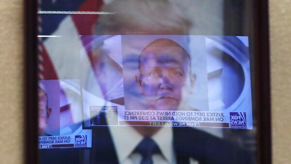 Televised pictures of parcel bombs suspect Cesar Sayoc are reflected in the official portrait of US President Donald Trump at the Justice Department in Washington DC, October 26, 2018 - Sputnik International