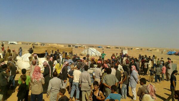 people gather to take basic food stuffs and other aid from community leaders at Rukban refugee camp - Sputnik International