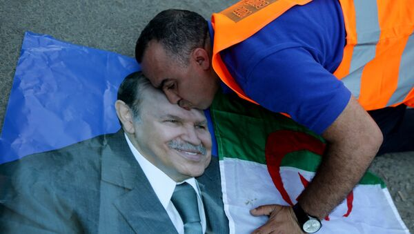 A supporter of Algerian President Abdelaziz Bouteflika kisses his picture as he celebrates in Algiers on April 18, 2014 after Bouteflika won a fourth term with 81,53% of the votes. - Sputnik International