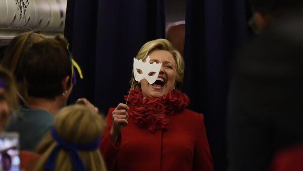 US Democratic presidential nominee Hillary Clinton smiles holding a mask onboard her campaign plane Erlanger, Kentucky, on October 31, 2016 - Sputnik International