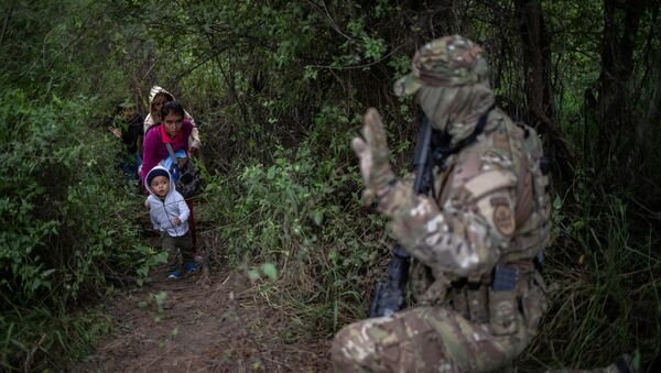 A member of the U.S. Border Patrol Tactical Unit (BORTAC) acknowledges family members after they illegally crossed the Rio Grande river into the United States from Mexico in Fronton, Texas, October 18, 2018 - Sputnik International