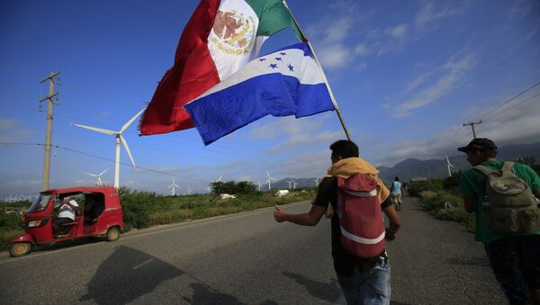 A migrant carrying the flags of Mexico and Honduras gives a thumbs-up to a moto rickshaw driver who stopped to take their picture, as a thousands-strong caravan of Central Americans hoping to reach the U.S. border moves onward from Juchitan, Oaxaca state, Mexico, Thursday, Nov. 1, 2018. Thousands of migrants resumed their slow trek through southern Mexico on Thursday, after attempts to obtain bus transport to Mexico City failed - Sputnik International