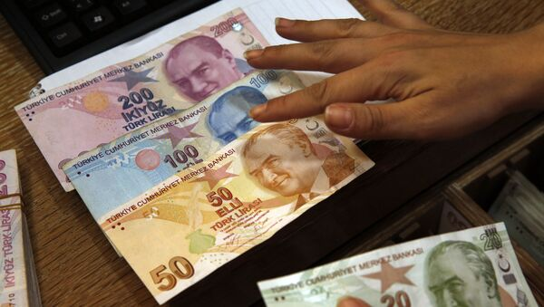 In this Wednesday, Aug. 15, 2018, file photo a worker at a currency exchange shop exhibits Turkish lira banknotes bearing pictures of modern Turkey's founder Mustafa Kemal Ataturk, in Istanbul.(file photo) - Sputnik International