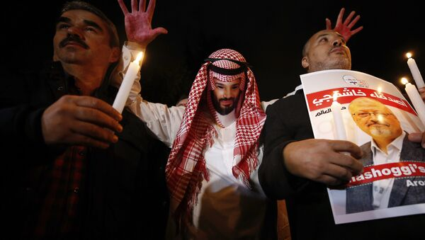 An activist, wearing a mask depicting Saudi Crown Prince Mohammed bin Salman, holds up his hands, painted with fake blood as he protests the killing of Saudi journalist Jamal Khashoggi, during a candlelight vigil outside Saudi Arabia's consulate in Istanbul, Thursday, Oct. 25, 2018 - Sputnik International