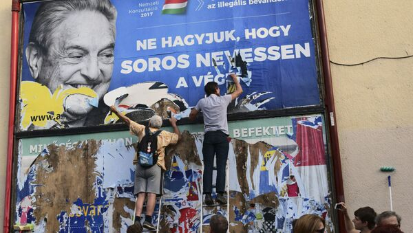 activists of the Egyutt (Together) party tear down an ad by the Hungarian government against George Soros, in Budapest, Hungary - Sputnik International