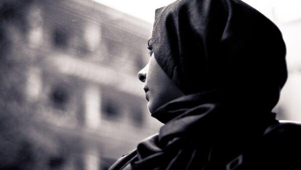 A woman wearing a hijab looks through the window - Sputnik International