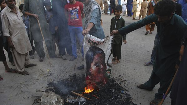 Pakistani protesters burn a poster image of Christian woman Asia Bibi, who has spent eight-years on death row accused of blasphemy and acquitted by a Supreme Court, in Hyderabad, Pakistan, Thursday, Nov. 1, 2018 - Sputnik International