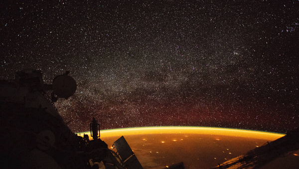 Astronaut aboard the International Space Station captures image of orange airglow enveloping Earth - Sputnik International