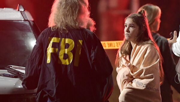An FBI agent talks to a potential witness as they stand near the scene Thursday, Nov. 8, 2018, in Thousand Oaks, Calif. where a gunman opened fire Wednesday inside a country dance bar crowded with hundreds of people on college night, wounding 11 people including a deputy who rushed to the scene - Sputnik International
