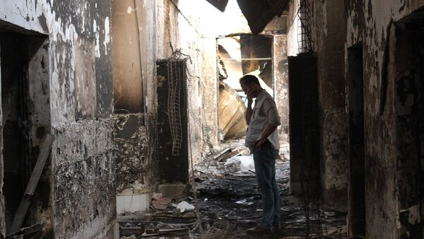 In this Friday, Oct. 16, 2015 photo, an employee of Doctors Without Borders walks inside the charred remains of their hospital after it was hit by a U.S. airstrike in Kunduz, Afghanistan - Sputnik International