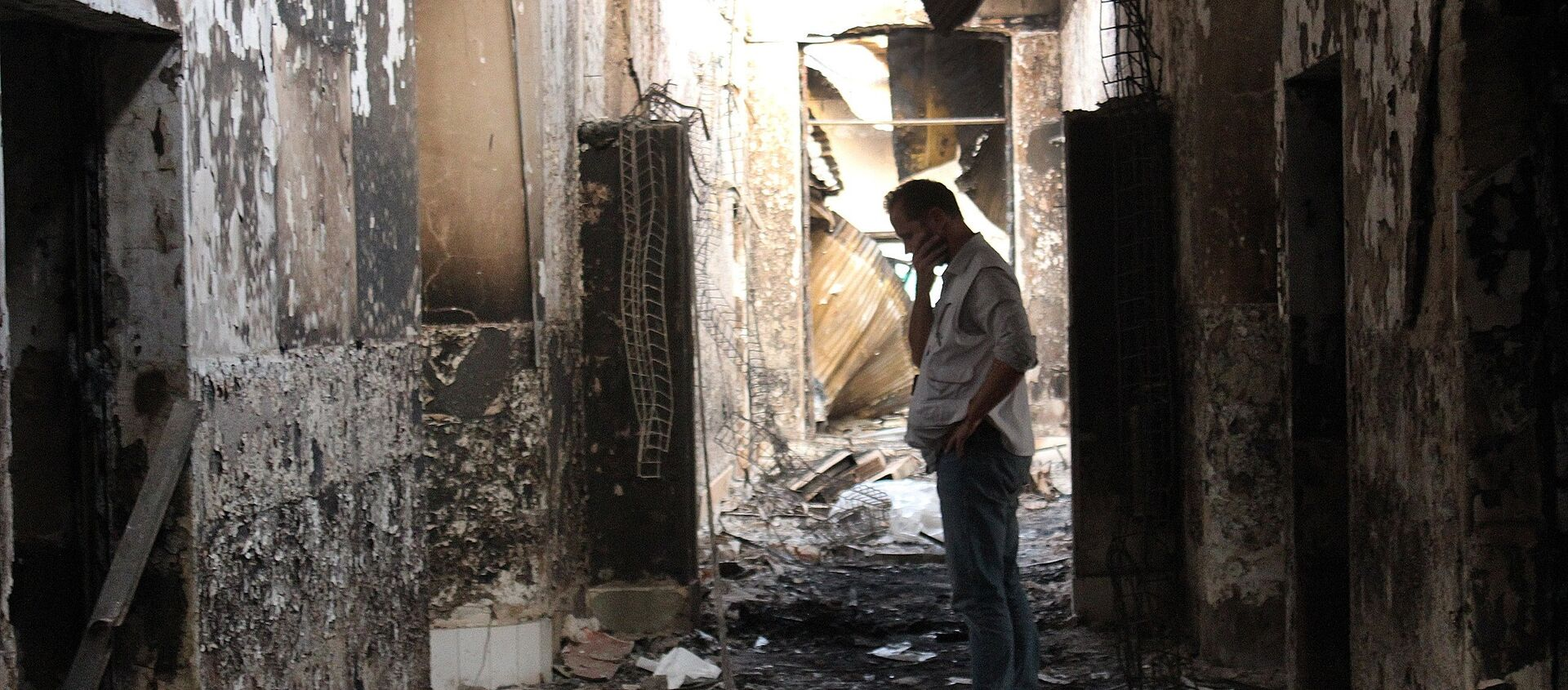 In this Friday, Oct. 16, 2015 photo, an employee of Doctors Without Borders walks inside the charred remains of their hospital after it was hit by a U.S. airstrike in Kunduz, Afghanistan - Sputnik International, 1920, 16.08.2021