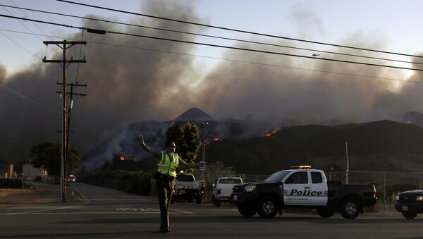 A police officer mans a checkpoint in front of an advancing wildfire Thursday, Nov. 8, 2018, near Newbury Park, Calif. The Ventura County Fire Department has also ordered evacuation of some communities in the path of the fire, which erupted a few miles from the site of Wednesday night's deadly mass shooting at a Thousand Oaks bar. - Sputnik International