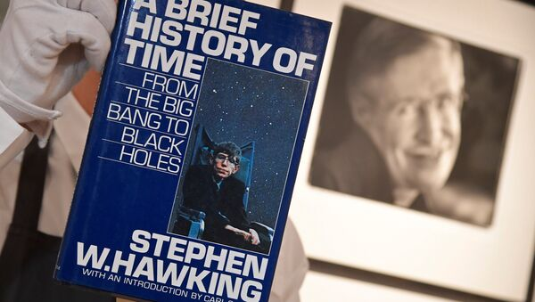 Fine-art handler Tom Richardson poses with a copy of A Brief History of Time which, has a thumb-print inside by author British theoretical physicist Stephen Hawking, ahead of an auction of items from Hawkinsg' personal estate at Christie's in London, Britain October 30, 2018. - Sputnik International