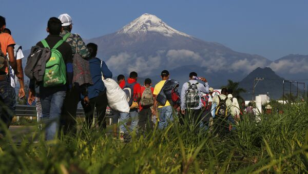 Central American migrants begin their morning trek as part of a thousands-strong caravan hoping to reach the U.S. border, as they face the Pico de Orizaba volcano upon departure from Cordoba, Veracruz state, Mexico, Monday, Nov. 5, 2018. A big group of Central Americans pushed on toward Mexico City from a coastal state Monday, planning to exit a part of the country that has long been treacherous for migrants seeking to get to the United States. - Sputnik International