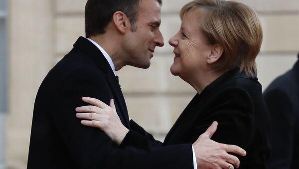 French President Emmanuel Macron hugs German Chancellor Angela Merkel in the courtyard of the Elysee Palace Sunday, Nov. 11, 2018 in Paris - Sputnik International