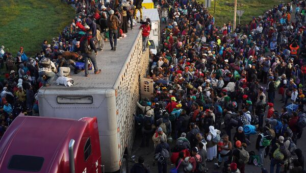 Migrants, part of a caravan of thousands traveling from Central America en route to the United States, try to catch a ride on a truck, in Irapuato, Mexico November 12, 2018 - Sputnik International