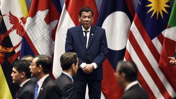 Philippine President Rodrigo Duterte waits on stage to pose with other leaders for a group photo before the start of the ASEAN-Plus Three (APT) summit on the sidelines of the 33rd Association of Southeast Asian Nations (ASEAN) summit in Singapore on November 15, 2018 - Sputnik International