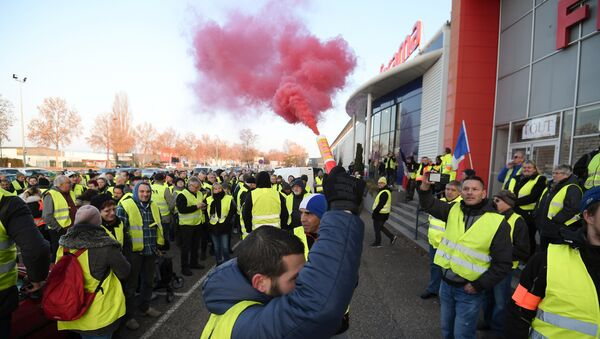 A demonstrators holds a flare during a demonstration of Yellow Vests (Gilets jaunes) against the rising of the fuel and oil prices on November 17, 2018 in Vendenheim, eastern France. - Sputnik International