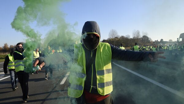 A man holds a flare as demonstrators wearing yellow vests (Gilets jaunes) protest against the rising of the fuel and oil prices on November 17, 2018 in Haulchien near Valenciennes, northern France. - Sputnik International