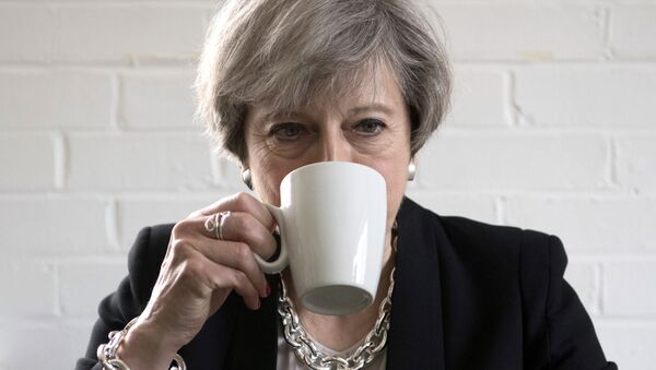 Britain's Prime Minister Theresa May drinks from a mug as she meets youth activists during a visit to the Young Minds mental health charity while on the election campaign trail, in London, Thursday May 11, 2017. Britain will hold a general election on June 8. - Sputnik International