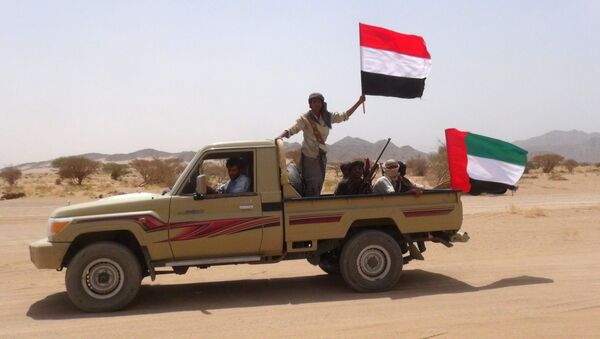 Yemeni tribesmen from the Popular Resistance Committees, supporting forces loyal to Yemen's Saudi-backed fugitive President Abedrabbo Mansour Hadi, hold the Emirati (R) and Yemeni flag as they drive in Marib province, east of the Yemeni capital, Sanaa, on September 20, 2015 - Sputnik International