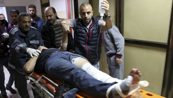 AP photographer Rashed Rashid rushed into the hospital by his colleagues after he was shot in the leg by an Israeli military sniper while filming a protest in Gaza. - Sputnik International