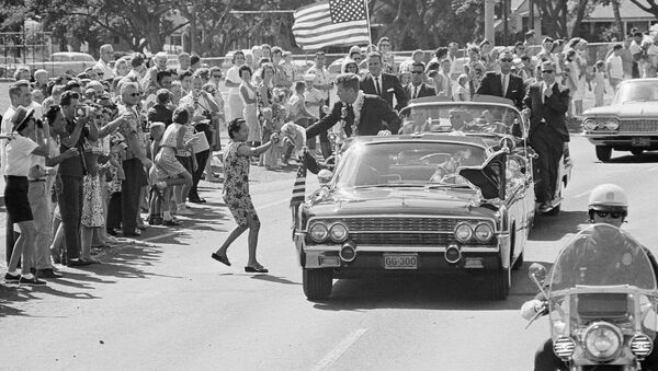 A woman runs into the street and tosses President John Kennedy a floral lei, which he caught,during a motorcade through Honolulu June 9, 1963 from the Pearl Harbor Naval Base to a Waikiki Beach Hotel where he made a strong plea for civil rights before a conference of the nation's mayors - Sputnik International