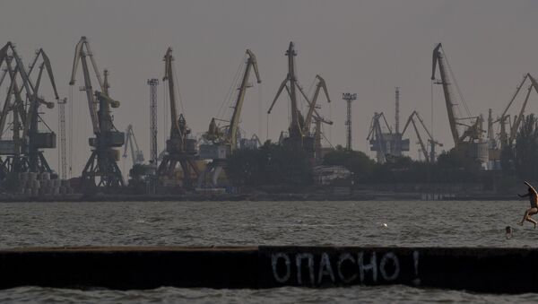 A man jumps in the Sea of Azov, backdropped by cranes of the commercial port, at dusk in Mariupol, Ukraine, Sunday, May 18, 2014 - Sputnik International