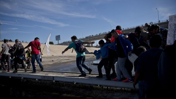 Migrants cross the river at the Mexico-U.S. border after getting past a line of Mexican police at the Chaparral crossing in Tijuana, Mexico, Sunday, Nov. 25, 2018 - Sputnik International