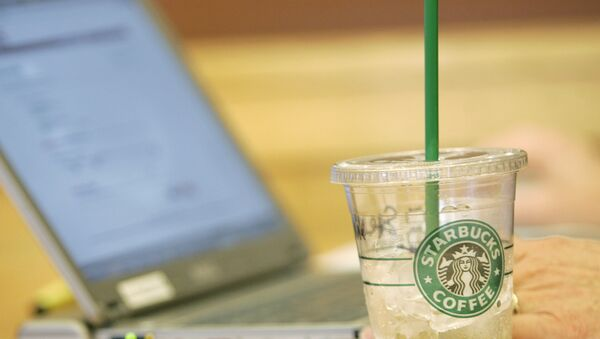 An iced drink sits next to a laptop computer in use Monday, Feb. 11, 2008, at a Starbucks Corp. store near the University of Washington in Seattle. Starbucks and AT&T Inc. will start offering a mix of free and paid wireless Internet service in most of the international coffee retailer's U.S. shops, beginning this spring. - Sputnik International