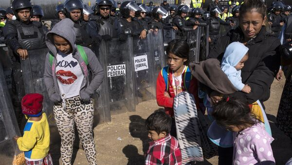 Migrants stand near Mexican police at the Mexico-U.S. border in Tijuana, Mexico, Sunday, Nov. 25, 2018, as they try to reach the US. - Sputnik International