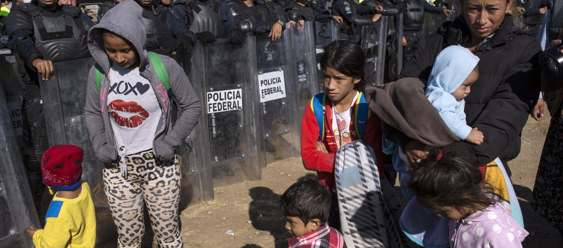 Migrants stand near Mexican police at the Mexico-U.S. border in Tijuana, Mexico, Sunday, Nov. 25, 2018, as they try to reach the US. - Sputnik International, 1920, 11.08.2021