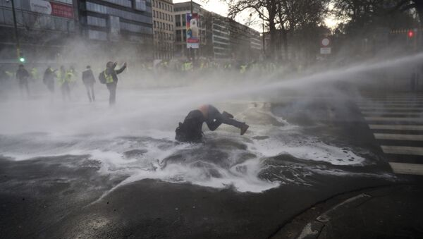 A demonstrator gets hit by a water cannon during a protest of the yellow jackets in Brussels, Friday, Nov. 30, 2018 - Sputnik International