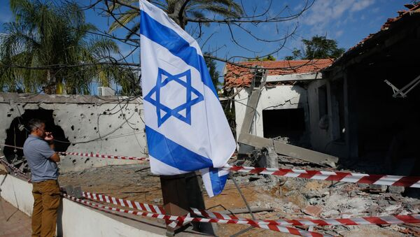 Israelis raise their national flag as they inspect the damage in a house caused by rockets fired from the Gaza Strip, in the southern Israeli town of Ashkelon, on November 13, 2018 - Sputnik International