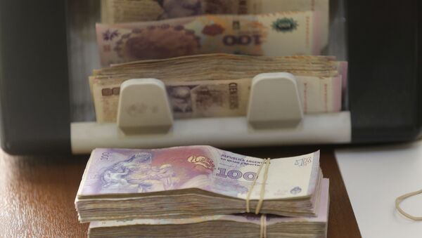 Argentine pesos from a client buying U.S. dollars are counted by a machine at an illegal exchange location in Buenos Aires, Argentina, Thursday, Dec. 17, 2015 - Sputnik International