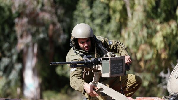 An Israeli soldier adjusts a weapon atop an armoured military ambulance near Israel's border with Lebanon - Sputnik International