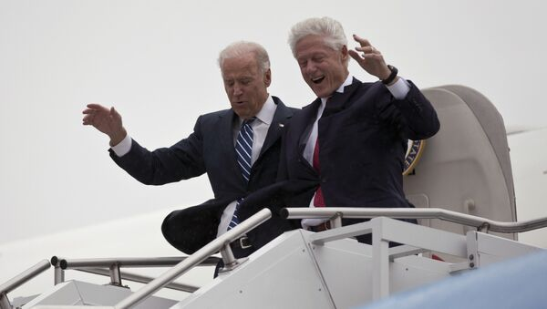 Vice President Joe Biden, left, accompanied by former President Bill Clinton walk carefully off Air Force Two during a rainstorm,, upon their arrival in Youngstown, Ohio, for a campaign stop, Monday, Oct. 29, 2012. - Sputnik International