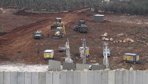 An Israeli military digger works on the Lebanese-Israeli border next to a wall that was built by Israel in the southern village of Kafr Kila, Lebanon, Tuesday, Dec. 4, 2018. - Sputnik International