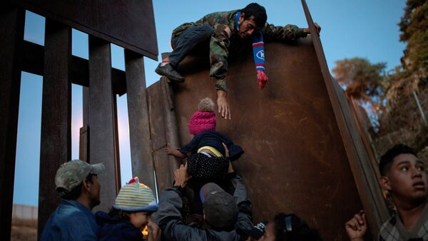 Migrants from Honduras, part of a caravan of thousands from Central America trying to reach the United States, try to jump a border fence to cross illegally from Mexico to the U.S, in Tijuana, Mexico, December 2, 2018 - Sputnik International