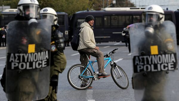 A man on a bike stands behind a police cordon guarding an anniversary rally marking the 2008 police shooting of 15-year-old student, Alexandros Grigoropoulos, in Athens - Sputnik International