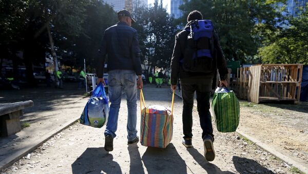 Migrants carry their belongings as they leave a makeshift camp for refugees outside the foreign office in Brussels, Belgium October 2, 2015 - Sputnik International