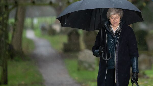 Britain's Prime Minister Theresa May shelters from the rain under an umbrella after attending a church service near to her Maidenhead constituency, west of London on December 9, 2018 - Sputnik International
