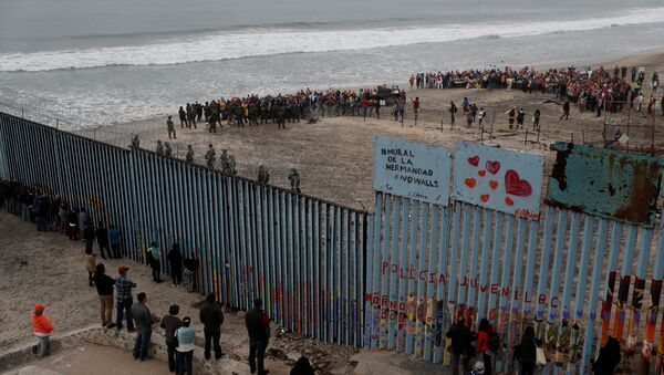 People take part in a gathering in support of the migrant caravan in San Diego, U.S., close to the border wall between the United States and Mexico, as seen from Tijuana, Mexico December 10, 2018 - Sputnik International