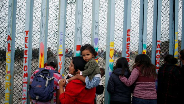 A woman carries her son as she looks at people taking part in a gathering in support of the migrant caravan in San Diego, U.S., close to the border wall between the United States and Mexico, in Tijuana, Mexico December 10, 2018 - Sputnik International