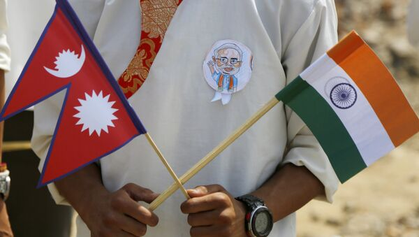 A school student holds a Nepalese and Indian flag and wears a badge with a portrait of Indian Prime Minister Narendra Modi as he waits to welcome Modi in Kathmandu, Nepal, Friday, May 11, 2018 - Sputnik International