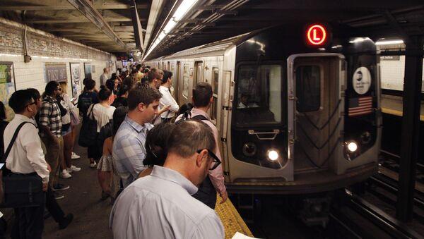 Commuters wait on a platform as the L subway train arrives in the 1st Avenue station. - Sputnik International