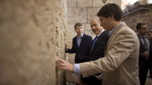 In this Jan. 22, 2013 file photo, Israeli Prime Minister Benjamin Netanyahu, center, prays with his sons Yair, background, and Avner, right, at the Western Wall, the holiest site where Jews can pray, in Jerusalem's Old City. Israeli political leaders are lashing out at Prime Minister Benjamin Netanyahu's eldest son for posting an anti-Semitic caricature aimed at his father's critics - Sputnik International
