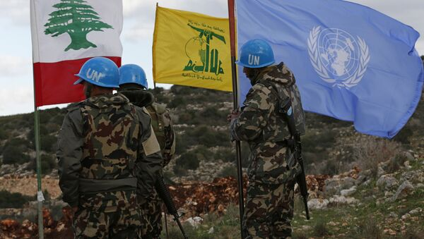 In this Thursday, Dec. 13, 2018 photo, UN peacekeepers hold their flag while standing next to Hezbollah and Lebanese flags, at the site where Israeli excavators are working, near the southern border village of Mays al-Jabal, Lebanon - Sputnik International