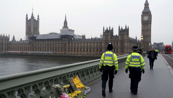 Police officers walk past floral tributes placed at the scene of an attack on Westminster Bridge, in London, Britain March 24, 2017 - Sputnik International